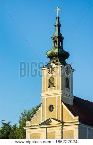 Urfahr Parish church in Linz upper Austria view of bell tower clock golden sunlight blues sky selective focus