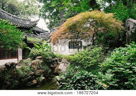 Traditional Chinese architecture building in a city park with rich vegetation of green foliage. Outdoor landscape view of Chinese style pavilion