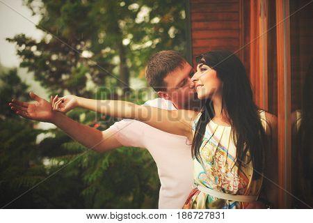 Man Kisses Woman's Cheek While She Cathes A Rain Drop
