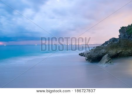 Long exposure photography of beach in the evening. Romantic atmosphere of peaceful night at sea, Bali island. Big rocks near smooth shoreline, pink horizon with sun rays, Indonesia outdoor landscape