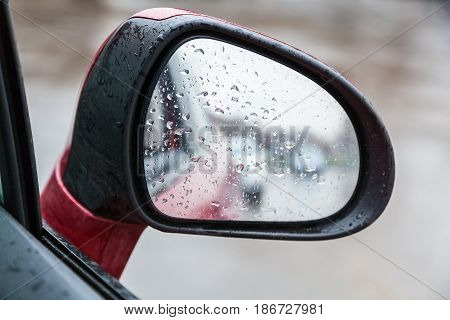 Raindrops On Side Rearview Mirror In Rainy Day