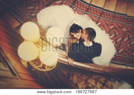 A Look From Above On The Newlyweds Kissing Under The Chandelier