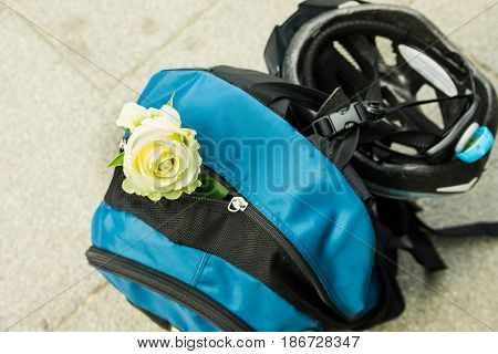 Blue backpack with buckled bicycle helmet and white rose adventure traveling romantic concept close up top view