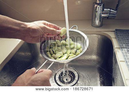 Men's hands wash the sieve fresh green beans in the kitchen