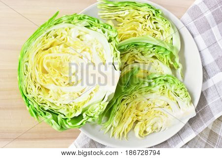 fresh green cut head of cabbage on ceramic gray plate, wooden and natural material background