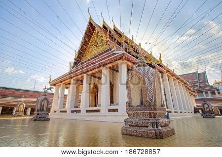 Traditional architecture of Buddhist temple with beautiful ornament with golden and red colors, colorful stupas in Bangkok at sunset time, Thailand landmark