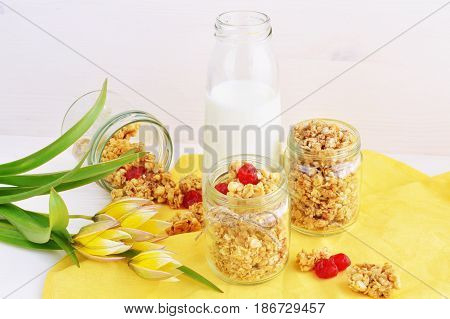 granola and crispy wholegrain crunchy with dry cherry milk in the bottle over yellow linen napkin wooden background