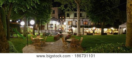 SAVIGLIANO, ITALY, MAY 30, 2010: Outdoor panoramic night view on inner garden of the Grantbaita hotel and italian restaurant patio. Italy holidays vacations tours famous hotels restaurants