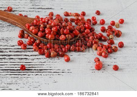 Rose pepper lay on white wooden table