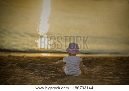 A little baby sits on the sand by the sea and admires the sunset
