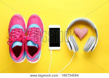 Sport Shoes With Smartphone And Headphones On Yellow Background