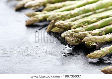 Green Asparagus With Water Drops On Black Wooden Table