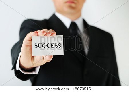 Businessman holding card with the word Success