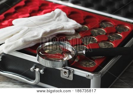 Different Collector's Coins In The Box With A Magnifying Glass And White Gloves