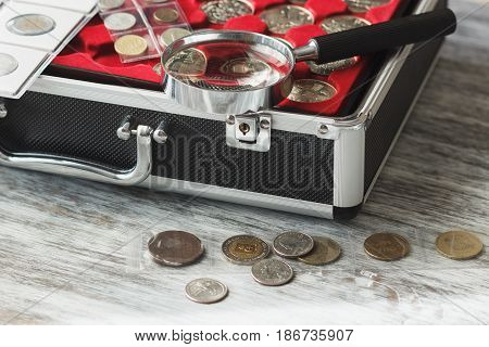 Different Collector's Coins In The Box With A Magnifying Glass