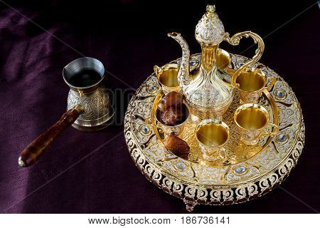 Still-life with traditional golden Arabic coffee set with dallah coffee pot and dates. Dark background. Horizontal photo