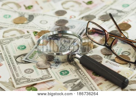 Ukrainian Hryvnia And American's Dollars With A Magnifying Glass