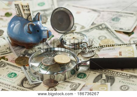 Ukrainian Hryvnia And American's Dollars With A Piggy Bank And Magnifying Glass