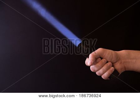 Male Hand Holding A Led Flashlight With A Narrow Purple Beam On A Black Background, Leaving The Righ