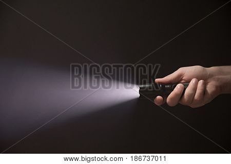 Male Hand Holding A Led Flashlight With A Wide White Beam On A Black Background, Leaving The Right S