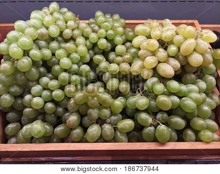 Large bunches of green fresh grapes on the market. Wine grapes close-up on the market. Fresh fruit detail.