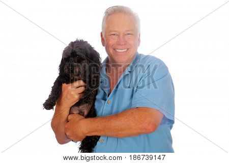 A handsome man holds a small black dog. Isolated on white. Room for text.
