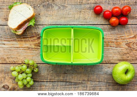 breakfast take away with lunchbox and fresh food on wooden table background top view