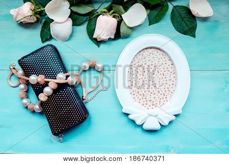 Spring background of bonded wooden boards layout on a blue wooden background with flowers photo frame purse and beads accessories