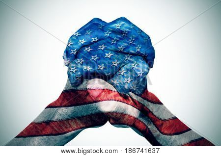 the clasped hands of a young caucasian man patterned with the flag of the United States on an off-white background, with a slide vignette added