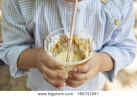 Little girl drinking milkshake at park. She is olding the glass with both hands