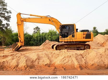 An excavator on a pile of sand