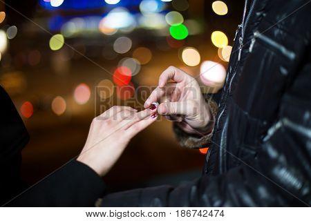 A Closeup Of A Man Putting An Engagement Ring