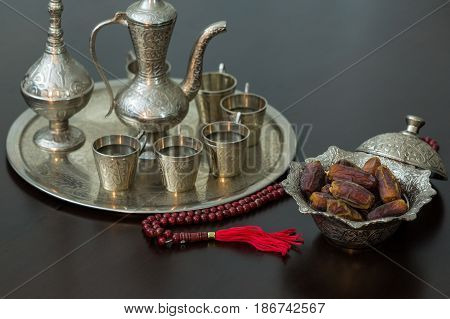 Ramadan concept: Dates zam zam water and rosary on brown table