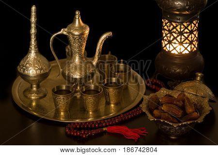Dates and zam zam water in darkness with oriental lantern