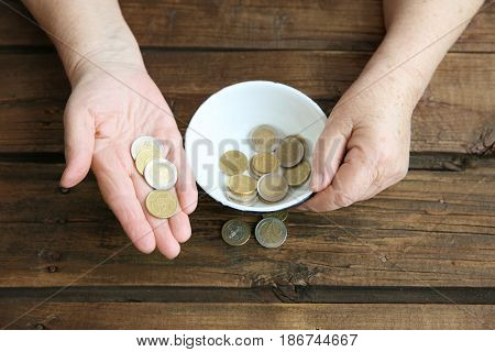 Hands of senior woman with bowl and coins on wooden background. Poverty concept
