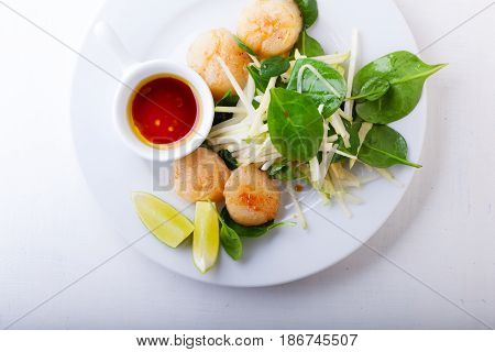Scallop Salad with greenery served on a white plate