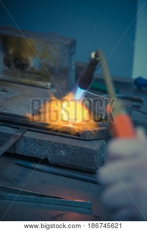 Goldsmith melting gold or silver with gas burner in wedding ring making process