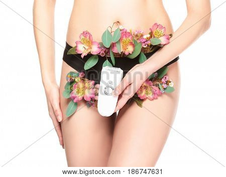 Beautiful young woman with plants and epilator on white background, closeup. Epilation concept