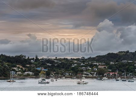 Bay of Islands New Zealand - March 7 2017: A major cyclone is building up over Paihia town set on a forested hill at the bay of the Pacific Ocean. Several pleasure boats on the water.