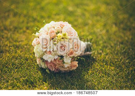 White Wedding Bouquet Lying On Green Grass