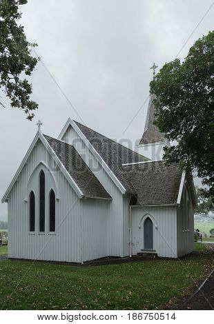 Bay of Islands New Zealand - March 7 2017: Historic first settlement mission church called Te Waimate. White church gray roof green trees and grass under silver sky.