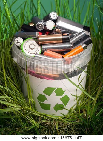 battery recycle bin with old element on wood table in grass