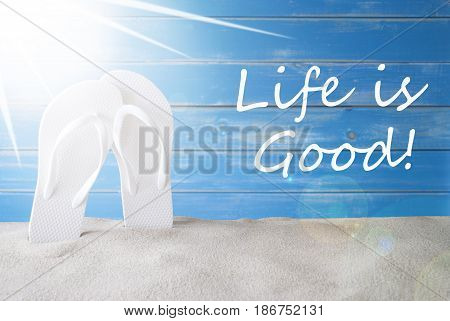 English Quote Life Is Good. Sunny Summer Greeting Card With Sand And Flip Flops. Blue Vintage And Shabby Chic Wooden Background.