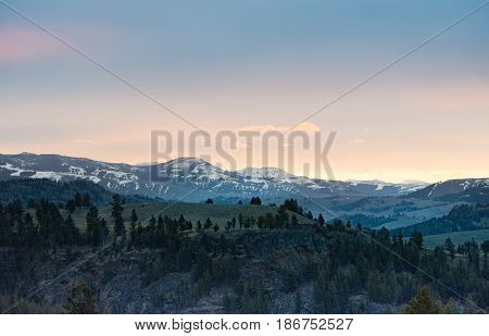 Panoramic view of sunrise over snow capped, rugged mountains with smaller rocky hills in the foreground. Photographed in natural light in Yellowstone National Park.