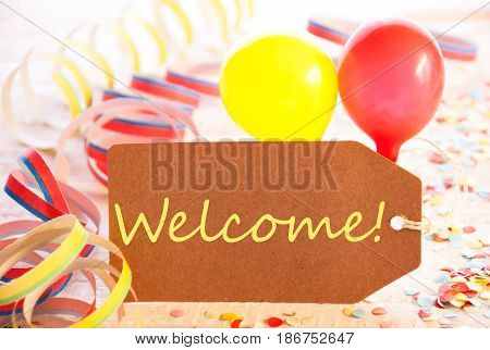 One Label With English Text Welcome. Party Decoration Like Streamer, Confetti And Balloons. Wooden Background With Vintage, Retro Or Rustic Syle