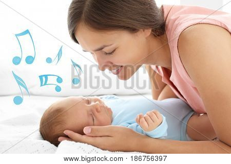 Mother with sleeping baby on bed. Lullaby songs and music concept