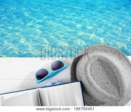 Reading during summer vacation. Book, sunglasses and hat on wooden pier near water