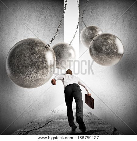 Businessman runs between iron balls. Overcoming obstacles to achieving success