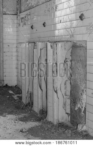 Crumbling-old urinals and a wall of white subway tiles, in an abandoned building, in black and white