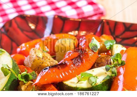Freshly grilled roasted mixed vegetables on a plate at the bbq picnic table
